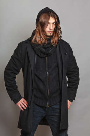 fall winter: Portrait of handsome fashionable man wearing black coat and scarf. Young guy posing in studio. Winter or autumn fashion. Stock Photo