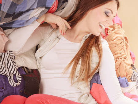 disorganized: Happy woman lying on sofa couch in messy living room. Young girl surrounded by many stack of clothes. Disorder and mess at home. Stock Photo