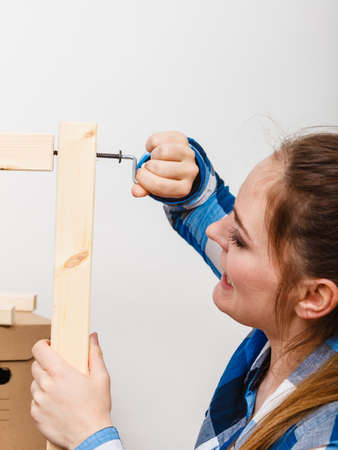 enthusiast: Woman assembling wood furniture using hex key. DIY enthusiast. Home improvement. Stock Photo
