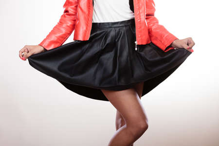 leather skirt: Fashion and style. Part body of mixed race woman wearing stylish red jacket coat and black leather skirt. Fashionable girl posing indoor. Stock Photo