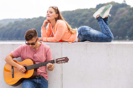 charmed: Love romance sound talent passion concept. Charmed girl enjoying music. Young lady listening to man playing guitar.