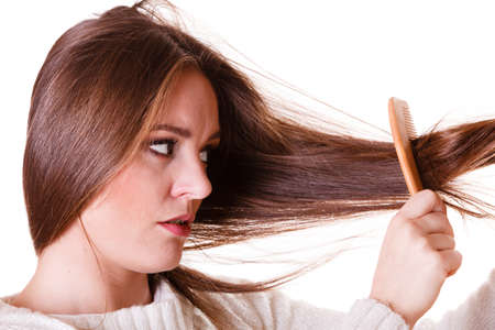 dissatisfied: Dissatisfied woman combing with brush and pulls at her long hair. Feeling pain for nice look in daily activity. Stock Photo