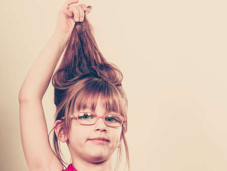 crazy hair: Play and fun. Charming little girl making funny crazy hair. Smiling lovely cute female child wearing glasses. Positive facial emotion.