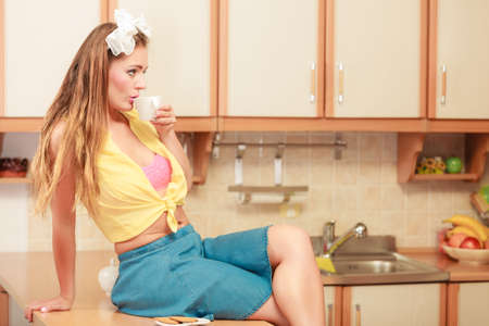 hairband: Pretty pin up girl with hairband bow drinking tea or coffee at home. Gorgeous young retro woman with hot beverage relaxing in kitchen. Stock Photo