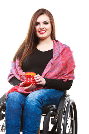 unrecognizable person: Real people, disability and handicap concept. Teen girl unrecognizable person sitting on wheelchair holding tea mug, studio shot on white Stock Photo
