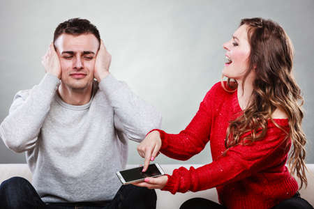 betray: Angry furious wife shouting at husband showing text messages from lover mistress on his mobile phone. Outraged girlfriend find out about boyfriend affair romance betrayal. Cheating man covering ears.