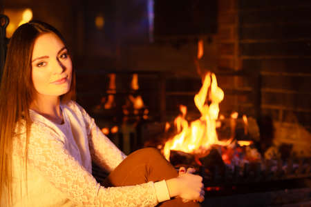 fireplace home: Woman relaxing resting at fireplace. Young girl heating warming up. Winter at home.