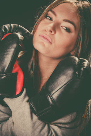 sportsmanship: Exercising prepare for fight. Sportsmanship and strong body. Young woman wear sportswear and boxing gloves. Stand with crossed hands look at opponent defend.