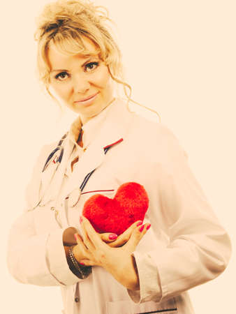 the cardiologist: Periodic examinations. Cardiology concept. Female cardiologist holding red heart. Middle aged doctor with stethoscope and white medical apron uniform. Filtered.