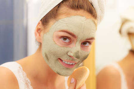 mud girl: Woman removing facial dried clay mud mask with sponge in bathroom in front of mirror. Skin care. Girl taking care of her complexion. Beauty spa treatment. Stock Photo