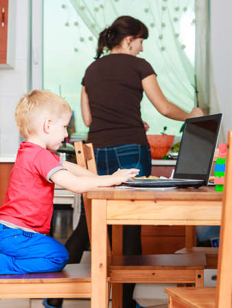 early education: Technology and early education. Spending time with family. Child use laptop for fun and learning. Boy with computer and mother cleaning house. Stock Photo