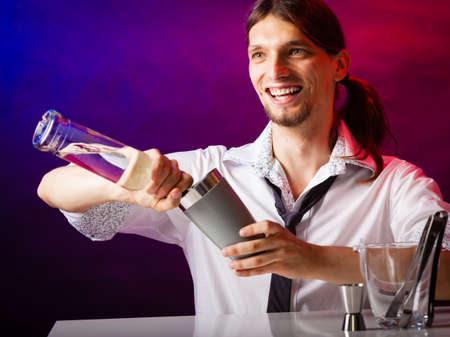 over the counter: Young stylish man bartender preparing serving alcohol cocktail drink over bar counter