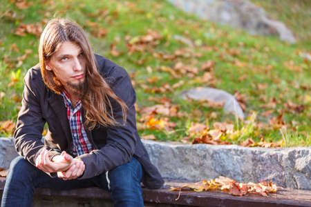 man with long hair: Man long hair sad thoughtful sitting on bench outdoor in autumnal park Stock Photo