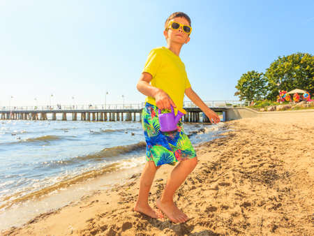 carelessness: Water fun and joy outside. Little boy walking through the sea ocean. Lonely kid playing outdoors in summer clothes. Stock Photo