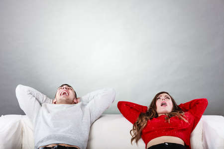 arms behind head: Happy, smiling young couple relaxing and yawning on couch at home. Calm, carefree man and woman resting with arms behind head. Healthy relationship.
