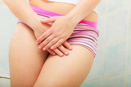 Les problèmes médicaux ou gynécologiques. Close up femme en culotte avec les mains tenant son entrejambe Banque d'images
