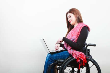 persona en silla de ruedas: La tecnología y los equipos móviles. Muchacha perjudicada personas de movilidad reducida con el ordenador portátil. Trabajador joven mujer de negocios en silla de ruedas. Foto de archivo