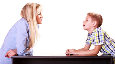 angry teacher: Relationships arguments and discussion. Mother and son sit at table and argue discuss solve problem. Stock Photo