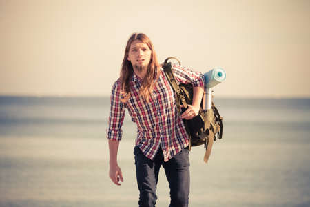 tramping: Man hiker backpacker walking with backpack by seaside at sunny day. Adventure, summer, tourism active lifestyle. Young long haired guy tramping Stock Photo