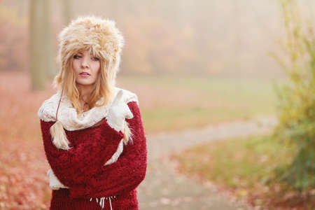 Portrait of pretty fashionable woman in fall forest park. Gorgeous young girl in fur winter hat and sweater pullover. Autumn fashion.