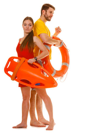 float tube: Lifeguards with rescue tube and ring buoy lifebuoy. Man and woman supervising swimming pool. Accident prevention.