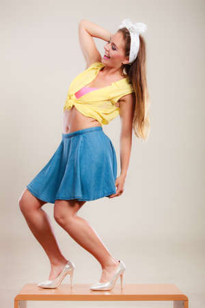 table skirt: Alluring seductive pretty pin up girl wearing hairband bow, skirt and high heels. Attractive gorgeous young retro woman dancing on table. Stock Photo