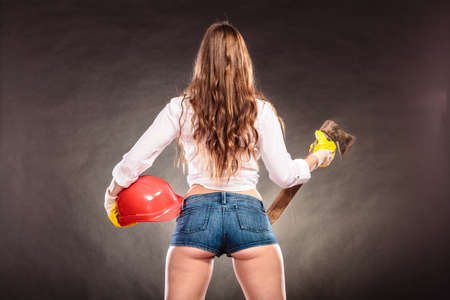 Sexy alluring woman holding axe chopper and helmet. Strong girl feminist working in man profession. Independent female. Rear view.
