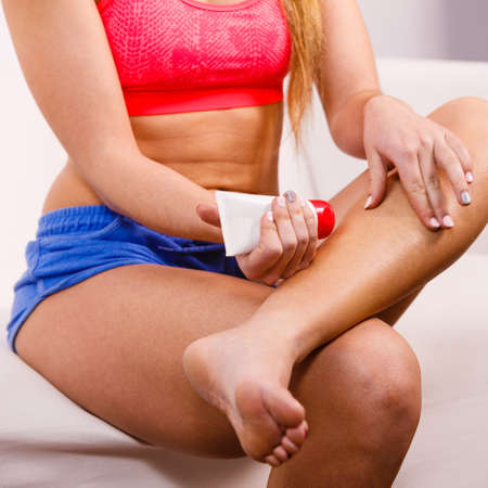 waxed legs: Woman putting ointment or moisturizer cream on her legs. Skin care
