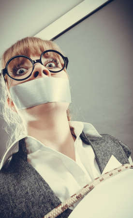 Afraid businesswoman bound by contract terms and conditions with mouth taped shut. Scared woman tied to chair become slave. Business and law concept. Stock Photo