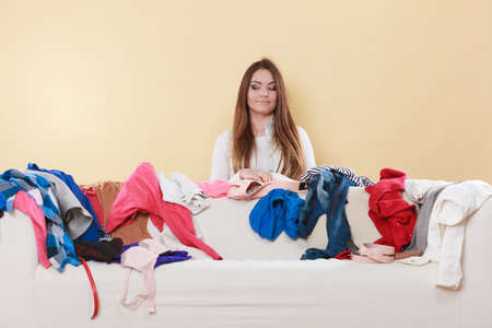 messy clothes: Happy woman behind sofa couch in messy living room. Young girl surrounded by many stack of clothes. Disorder and mess at home. Stock Photo
