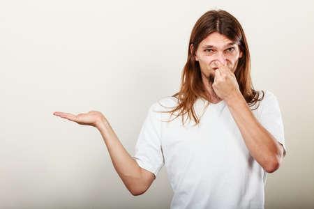 oler: Expresión de muy mal olor. Joven de pelo largo sudorosa toma de la mano del hombre gesto de la mano empyt abierta para el producto. concepto de la sudoración.