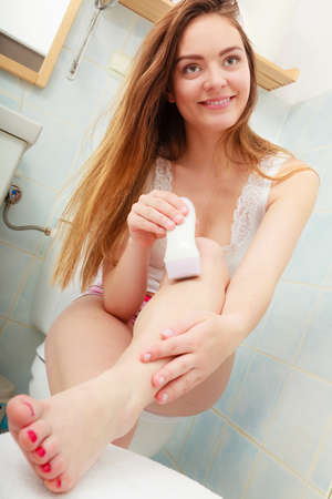 depilate: Hygiene skin body care concept. Hair removal. Closeup woman shaving legs with electric shaver depilator in bathroom Stock Photo