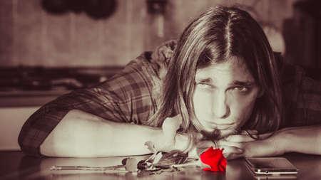 decepci�n: La decepci�n y la depresi�n. el concepto de amor no correspondido. Hombre joven preocupante decepcionado con Rosa roja, smartphone telefono esperando a su novia.