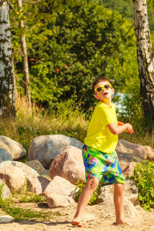 enjoyable: Play and fun concept. Little playful enjoyable boy kid throwing flying disc. Male child having fun playing outdoor on beach.