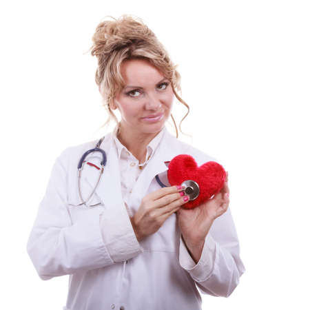 proffesional occupation: Medical examination of cardiology. Middle aged cardiologist with heart and stethoscope. Female doctor in white uniform makes measurement heartbeat. Isolated on white. Stock Photo