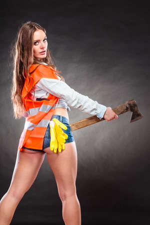 alluring: Sexy alluring woman wearing helmet and safety workwear holding axe chopper. Strong girl feminist working in man profession. Independent female. Stock Photo