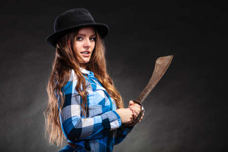 machete: Pretty gorgeous woman holding machete. Strong girl feminist wearing checked shirt and hat.