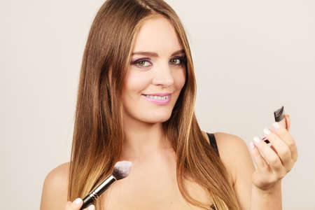facial painting: Woman applying rouge with brush to her face. Pretty gorgeous girl beautifying. Fashion and makeup Stock Photo