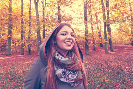 ginger hair: Nature, outdoors concept. Ginger hair girl in the forest. Young lady is enjoying good autumnal weahter. Stock Photo