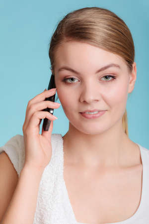 morning routine: Morning routine busy day. Young woman after shower talk on cell phone. White towel on shoulder. Stock Photo