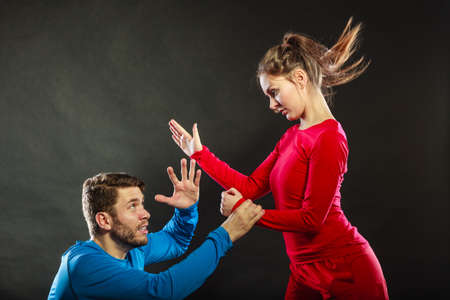 aggresive: Wife abusing husband. Aggresive woman beating slapping scared man. Couple in studio on black. Domestic violence aggression. Bad relationship.