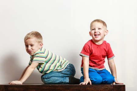 frendship: Free time, fun and independence. Little boys play together indoors sit on table. Blonde children wear colorful clothes. Stock Photo