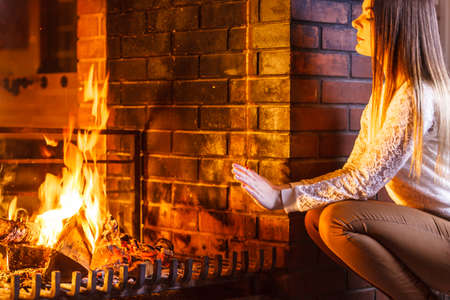 fireplace home: Woman warming hands up at fireplace. Young girl relaxing resting. Winter at home.