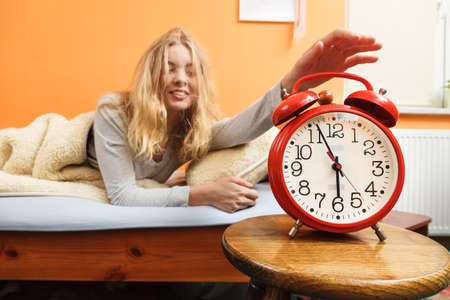 turning off: Woman waking up in bed turning off alarm clock. Young girl in the morning.