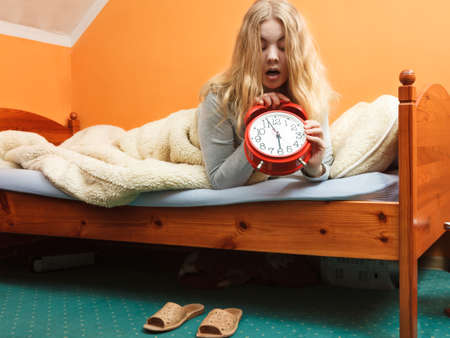 turning off: Panic woman waking up late in morning turning off alarm clock. Young girl laying in bed.