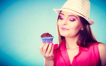 indulging: Sweet food sugar make us happy. Smiling woman summer clothing holds cake chocolate muffin in hand blue background