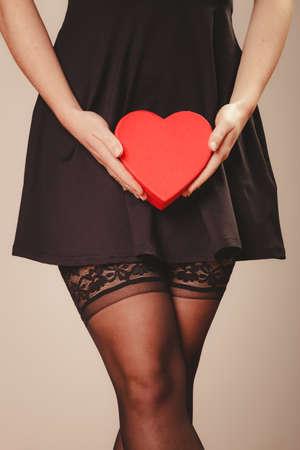 sexualidad: La belleza, la sexualidad y la seducci�n. Mujer parte del cuerpo sexy con un vestido negro y medias de las bragas de la celebraci�n de caja de regalo presente coraz�n rojo en las manos. estudio de disparo.