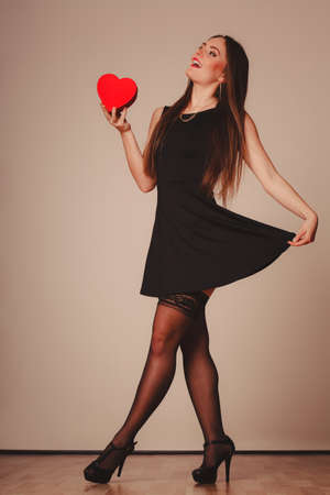 full lenght: Beauty, sexuality and seductiveness. Young attractive sexy full lenght woman model with red heart box gift present dancing in studio.