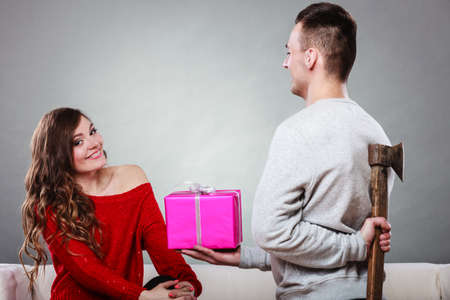 betray: Sneaky insincere man holding axe giving gift present box to woman. Husband concealing hiding his true feelings from happy trusting wife. Untrue False intention. Relationship problems.
