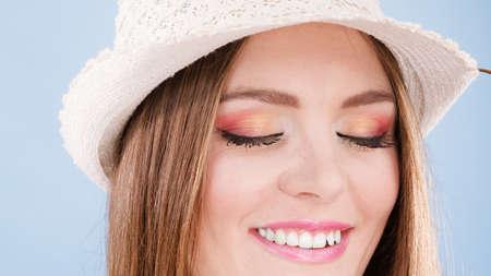 Fronte della donna occhio trucco colorato chiuso cappello occhi di paglia sulla testa sorridendo divertirsi primo piano. modo di estate, girato in studio su sfondo blu